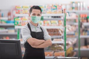a supermarket employee wearing a covid mask